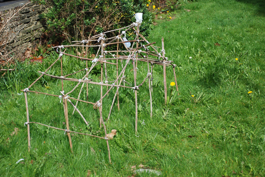 a resident's front garden 'twig house' made from found objects